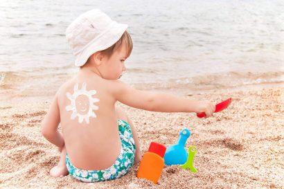 Niño jugando en la playa con la piel expuesta.